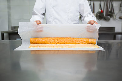 Chef preparing pastry roll with baking paper - p1166m2130305 by Cavan Images