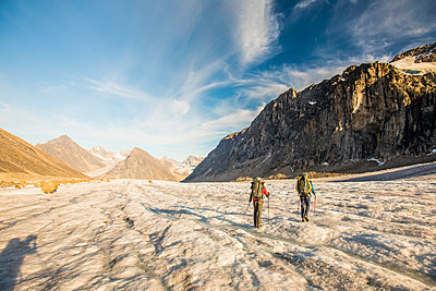 Rear view of backpackers crossing glacier - p1166m2205807 by Cavan Images