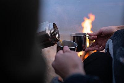 Crop couple pouring tea near campfire - p1166m2235282 by Cavan Images