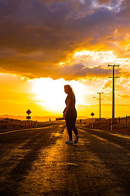 Woman walks on a road at sunrise - p1455m2204839 by Ingmar Wein