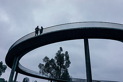 Two businessmen standing on dark bridge, having a meeting - p300m1537543 by Kniel Synnatzschke