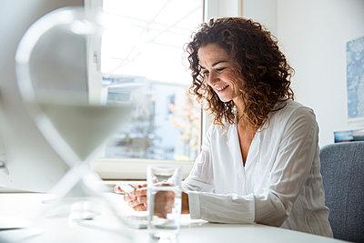 Businesswoman using smartphone in office - p300m2069894 von Robijn Page
