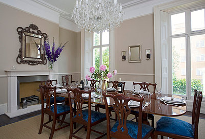 Chandelier above set dining table in London townhouse - p3493648 by Robert Sanderson
