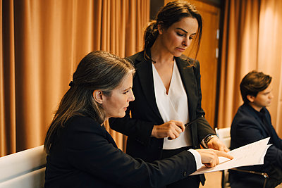 Businesswoman brainstorming storming over legal document with female lawyer in office - p426m2270845 by Maskot