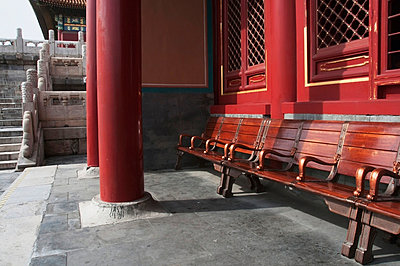 Wooden seating outside a building with a red wall and red pillars;Forbidden city beijing china - p442m767755f by Diane Levit