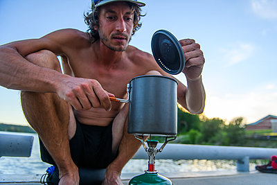 Man cooking on camping stove - p924m2252886 by Alex Eggermont