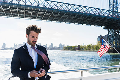 USA, New York City, businessman on ferry on East River checking cell phone - p300m1191604 by Uwe Umstätter