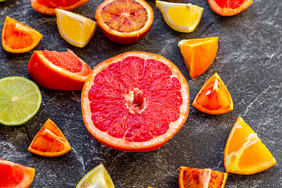 Sliced citrus fruits on slate - p300m2083948 by Sandra Roesch