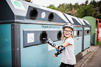 Girl putting rubbish into recycling bin - p312m2190995 by Anna Johnsson
