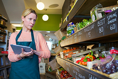 Grocer using tablet computer in store - p429m662141f by Frank van Delft
