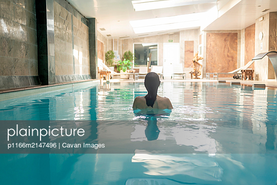 Rear view of a woman relaxing in spa pool - p1166m2147496 by Cavan Images