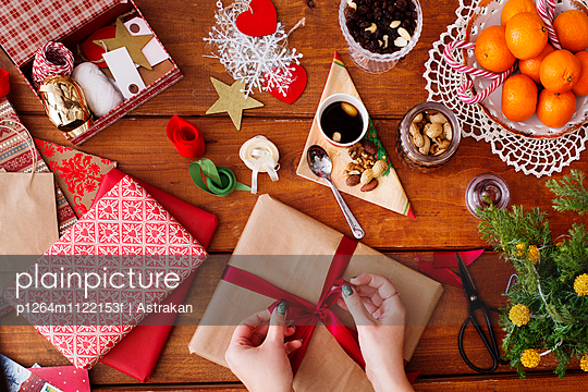 Cropped image of hands tying bow on Christmas present at wooden table - p1264m1122153f by Astrakan