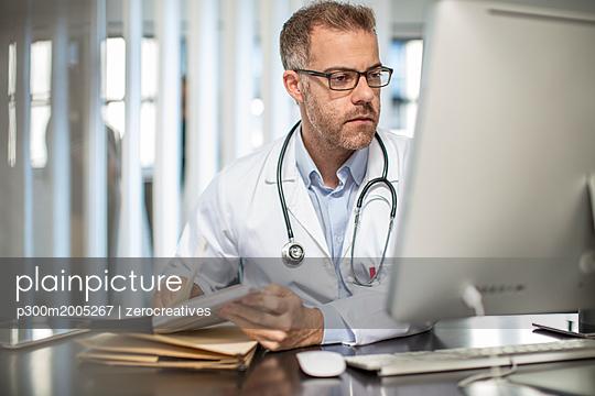 Doctor working at desk in medical practice - p300m2005267 von zerocreatives