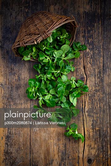 Lamb's lettuce and wickerbasket on wood - p300m2080874 by Larissa Veronesi