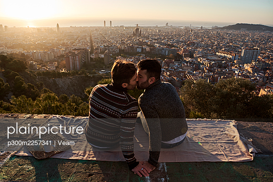 Gay men kissing while sitting on observation point against cityscape, Bunkers del Carmel, Barcelona, Spain - p300m2257341 by Veam