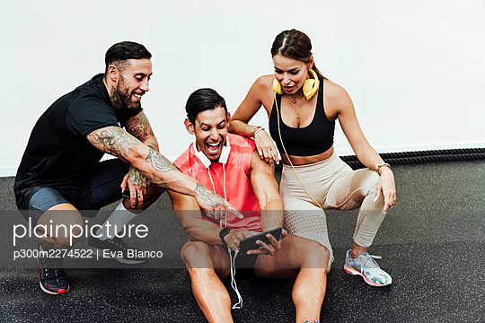Sportsman laughing while using mobile phone by friends in gym  - p300m2274522 by Eva Blanco