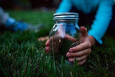 Cropped hands of boy holding glass jar with firefly on grassy field - p1166m1576681 by Cavan Images