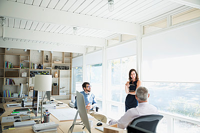 Architects meeting talking in sunny office - p1192m1194186 by Hero Images