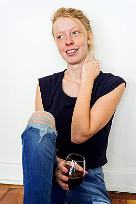 Ginger woman sitting on floor at home, drinking red wine - p300m1449557 by Valentina Barreto