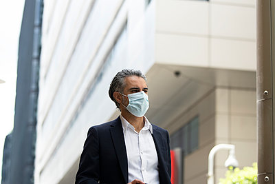 Businessman wearing protective mask in city - p300m2206951 by Pete Muller