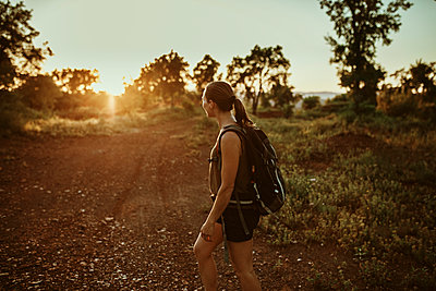 Female trekker looking at sunset view while standing in forest - p300m2214048 by David Molina Grande
