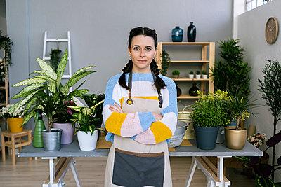 Young woman working in a gardening laboratory or plant shop - p300m2275343 von Giorgio Fochesato