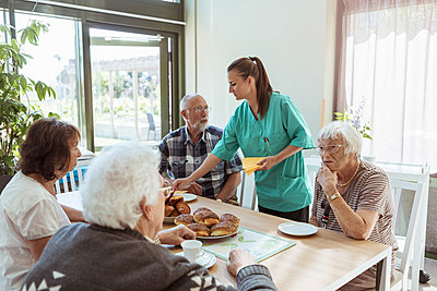 Elderly care nurse serving meal to people at table in nursing home - p426m2072564 by Kentaroo Tryman