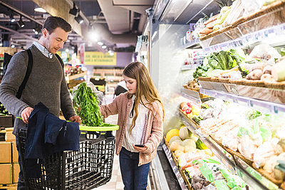 Daughter putting food in shopping cart held by father in grocery store - p426m2097631 by Maskot