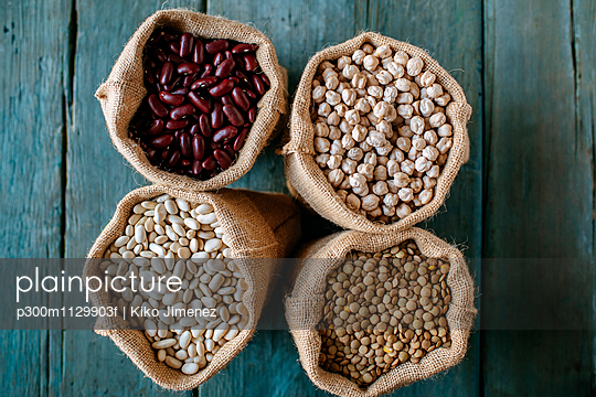 Four sacks of dried brown lentils, chickpeas and red and white beans on wood - p300m1129903f von Kiko Jimenez