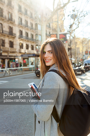 Spain, Barcelona, portrait of smiling young woman with backpack standing at street - p300m1587065 von Valentina Barreto