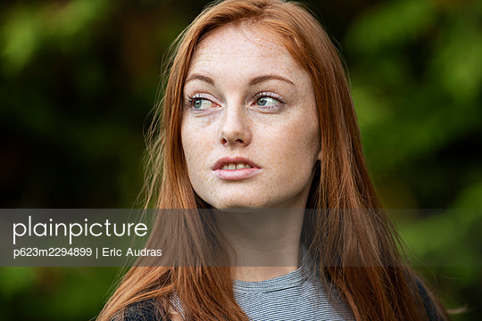 Anxious young woman sitting in public park - p623m2294899 by Eric Audras