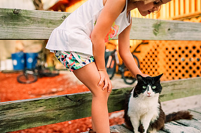 Young girl bending down to pet black and white cat - p1166m2094921 by Cavan Images