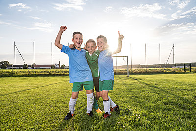 Young football players cheering on football ground - p300m1580832 by Fotoagentur WESTEND61