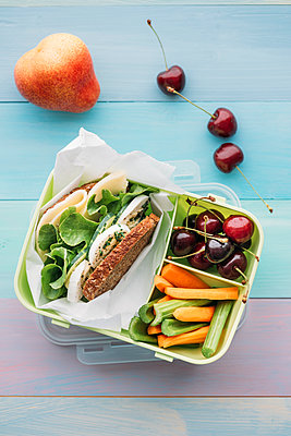 Healthy school food in a lunch box, vegetarian sandwich with cheese, lettuce, cucumber, egg and cress, sliced carrot and celery, cherries and pear - p300m2023984 by Ina Peters