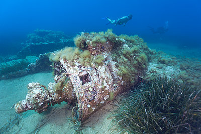 Propeller of sunken airplane wreck with scuba diver swimming in background - p300m2143276 by Christian Zappel