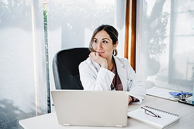 Smiling female medical professional with hand on chin day dreaming while sitting at desk - p300m2265694 by Eva Blanco