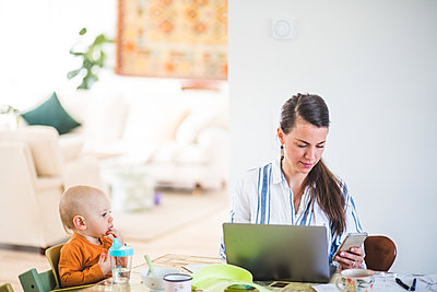 Baby girl looking at busy working mother while sitting at table in home office - p426m2117015 by Maskot
