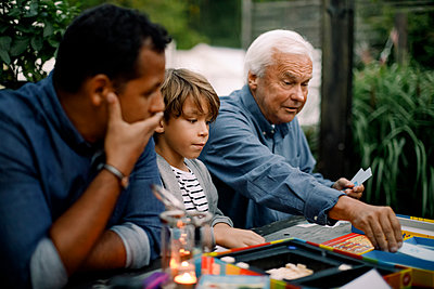 Multi-generation family playing board game while sitting at table in backyard - p426m2159675 by Maskot