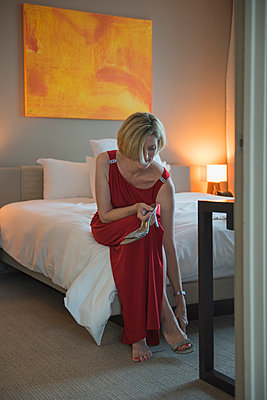 Caucasian woman removing shoes in bedroom - p555m1411585 by Chris Sattlberger