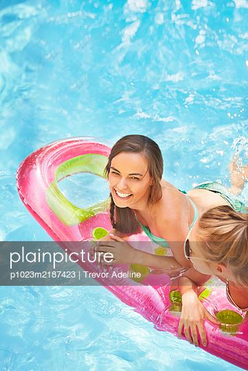 Portrait smiling women friends floating on pool raft in summer swimming pool - p1023m2187423 by Trevor Adeline