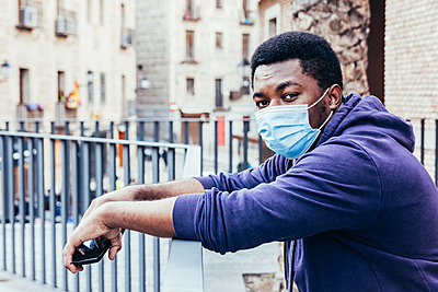 Portrait of an African American boy with face mask leaning against a fence in the city. - p1166m2254932 by Cavan Images