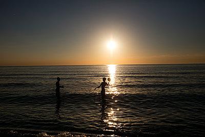 Kinder spielen mit dem Ball im Meer in der Abendsonne - p1212m1171652 von harry + lidy