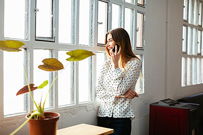 Happy young woman on cell phone at the window in office - p300m1587039 by Bonninstudio