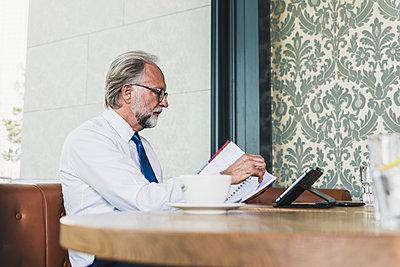 Mature businessman working at table in a cafe - p300m1587913 von Uwe Umstätter