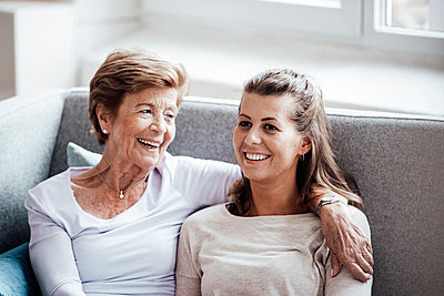 Smiling young woman with arm around grandmother looking away while sitting on sofa - p300m2276878 by Gustafsson