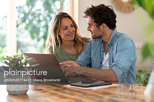 Smiling couple looking at each other while sitting in front of laptop at table - p300m2277441 by Steve Brookland