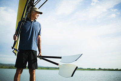 A middle-aged man carrying oars and a rowing shell on his shoulder.  - p1100m876293f by Jamie Kripke