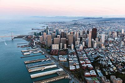 Aerial view of modern buildings by sea against sky during sunset - p1166m1230533 by Cavan Images