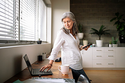 Creative businesswoman using laptop and smart phone in office - p1192m2124187 by Hero Images