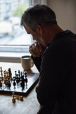 Attentive man playing chess - p1315m1229951 by Wavebreak